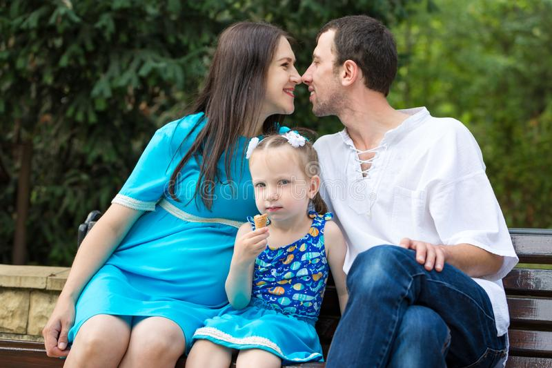 Family sitting on a bench in park. Little girl eating a waffle cup. Woman pregnant. Happy family life concept royalty free stock image
