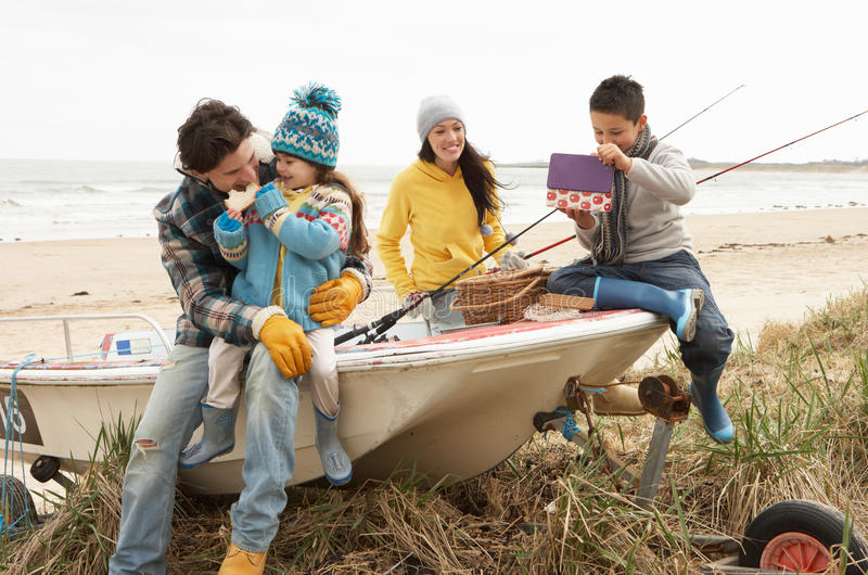 Download Family Sitting On Boat With Fishing Rod On Beach Stock Image - Image: 16133727