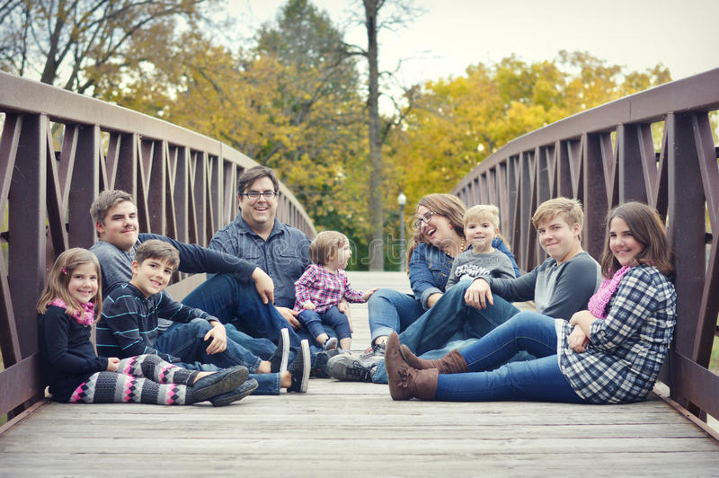 Family Sitting on a bridge. A large family consisting of a mom, dad and seven children, four boys and three girls, sitting on a bridge royalty free stock photo