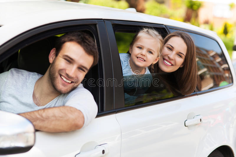 Family sitting in the car looking out windows. Happy family sitting in the car