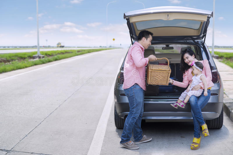 Family sitting in car with picnic basket. Happy family sitting behind the car while holding picnic basket in the highway stock image