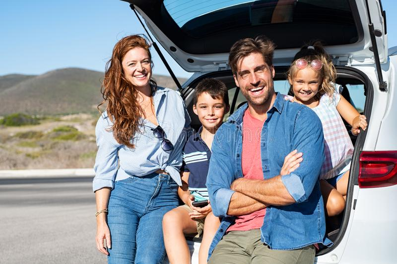 Family sitting in car trunk royalty free stock image