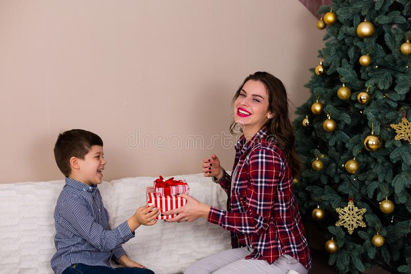 Family sitting by the Christmas tree royalty free stock image