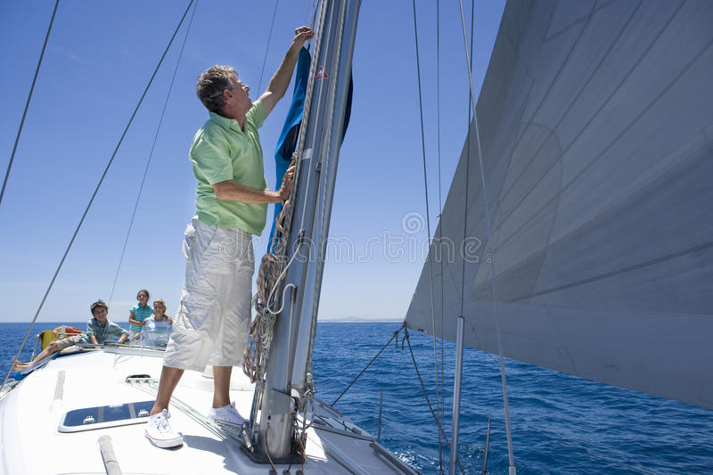 Family sitting on deck of sailing boat out to sea, watching father adjusting sail mast rigging in foreground, side view royalty free stock photography