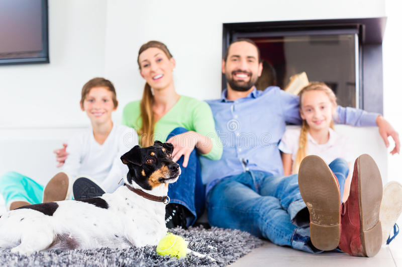 Family sitting with dog at living room floor fireplace. Family sitting together with dog on living room floor at fireplace stock photos
