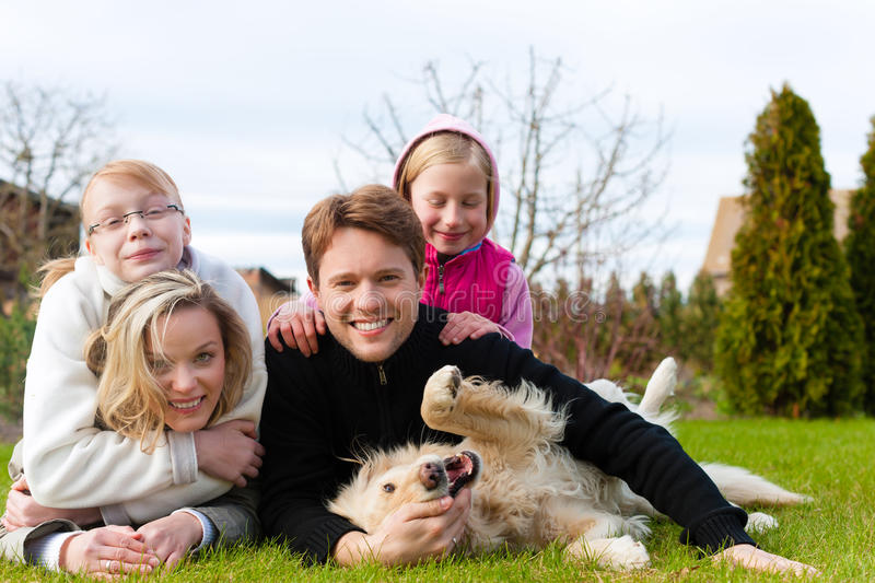 Family sitting with dogs together on a meadow royalty free stock image