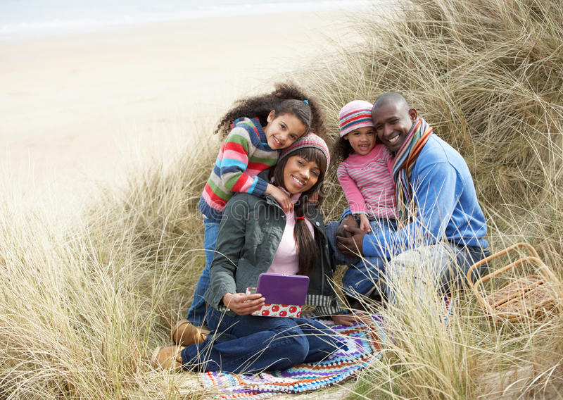 Family Sitting In Dunes Enjoying Picnic On Winter. Beach Smiling stock photography