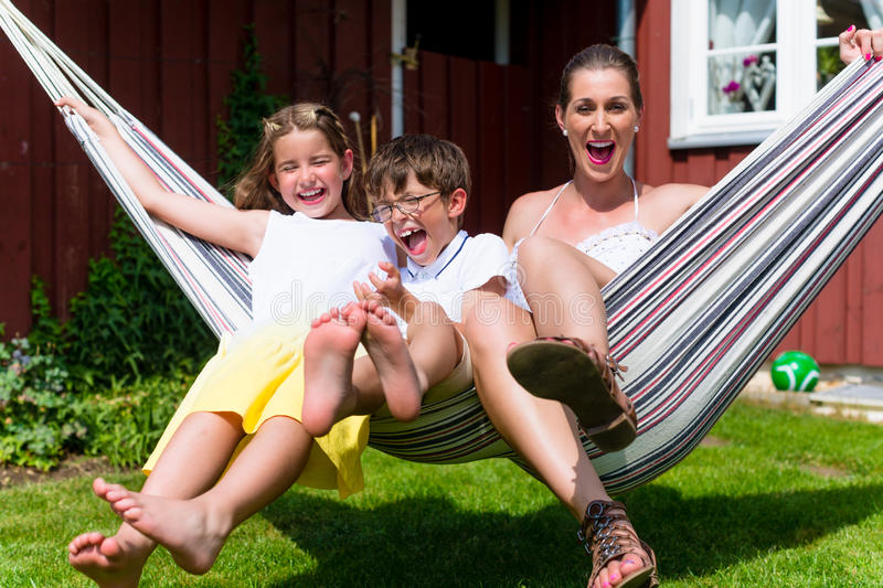 Family sitting in hammock in front of home. Family of mother and kids sitting in hammock in front of home stock photo