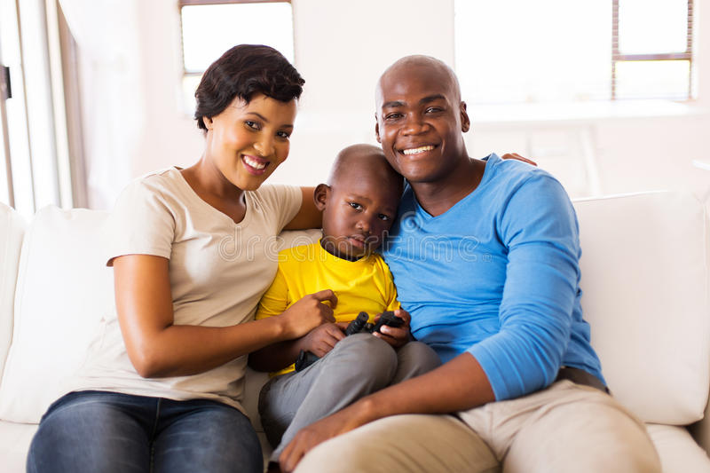 Family sitting home. Happy african american family sitting on the couch at home stock photos