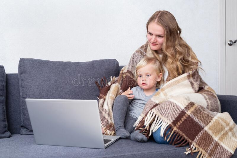 A family is sitting at home with a laptop. Mom with a small son under the blanket watch online cartoons programs. Coronavirus,. Quarantine, stay home concept stock photo