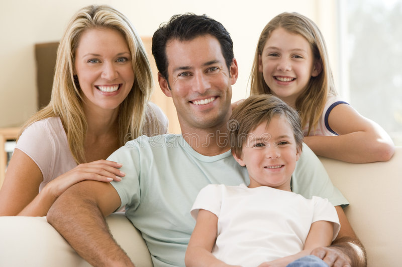Family Sitting In Living Room Smiling Royalty Free Stock Images