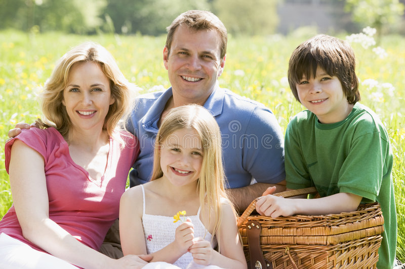 Family sitting outdoors with picnic basket smiling royalty free stock images