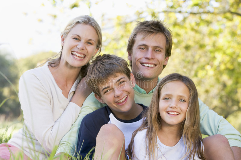 Family sitting outdoors smiling royalty free stock image