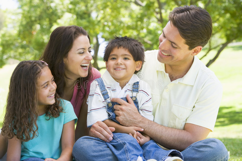 Family sitting outdoors smiling royalty free stock photo