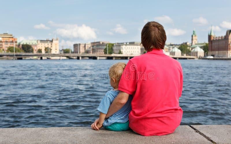 Family sitting on pier stock image