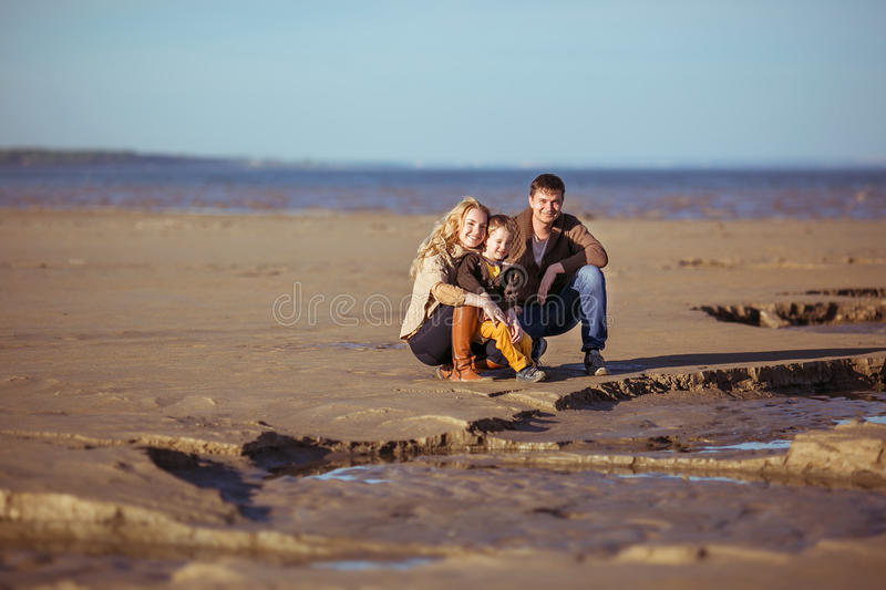 The family is sitting on the sand and smiling stock image