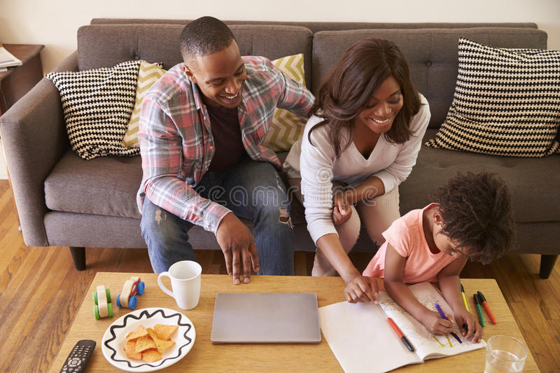 Family Sitting On Sofa As Daughter Colors In Picture Book royalty free stock photography