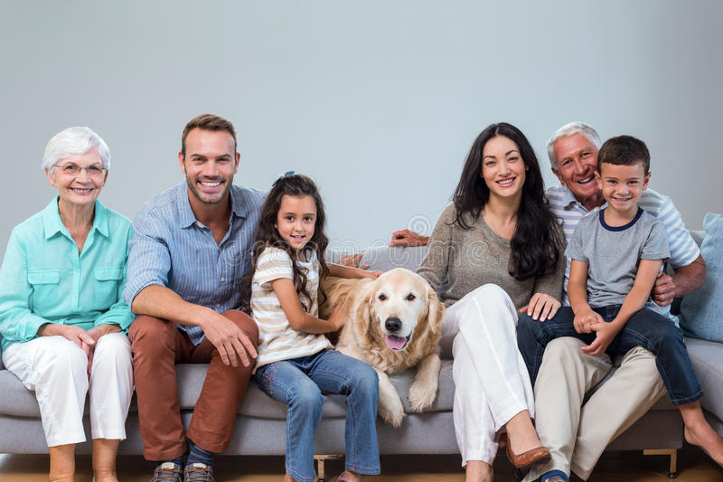 Family sitting on sofa with dog stock photos