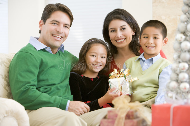 Family Sitting On Sofa Holding A Christmas Gift stock photo