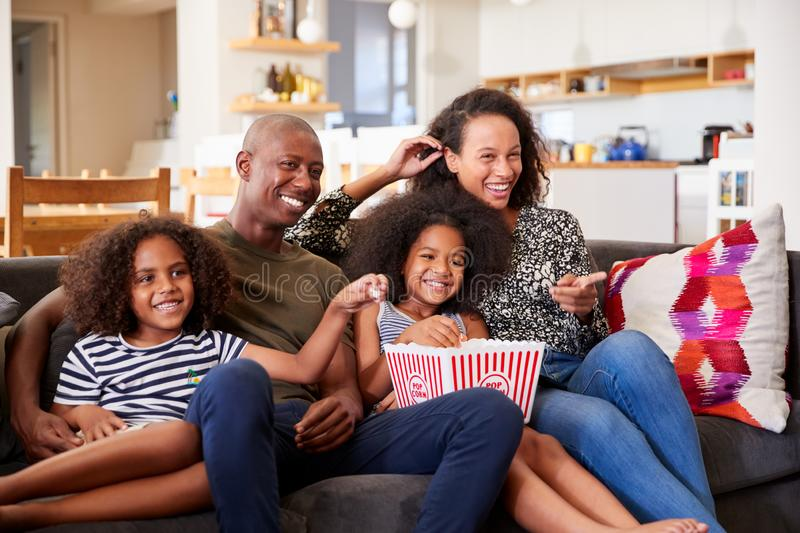 Family Sitting On Sofa At Home Eating Popcorn And Watching Movie Together stock photography