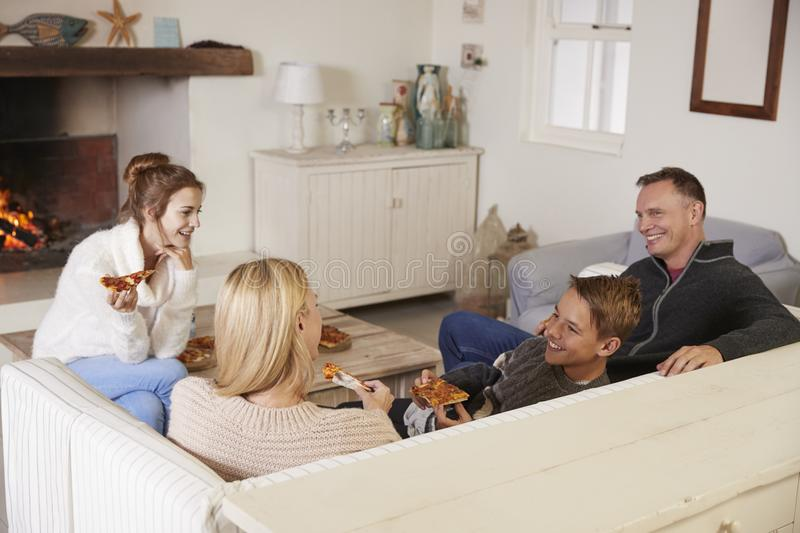 Family Sitting On Sofa In Lounge Next To Open Fire Eating Pizza royalty free stock photography