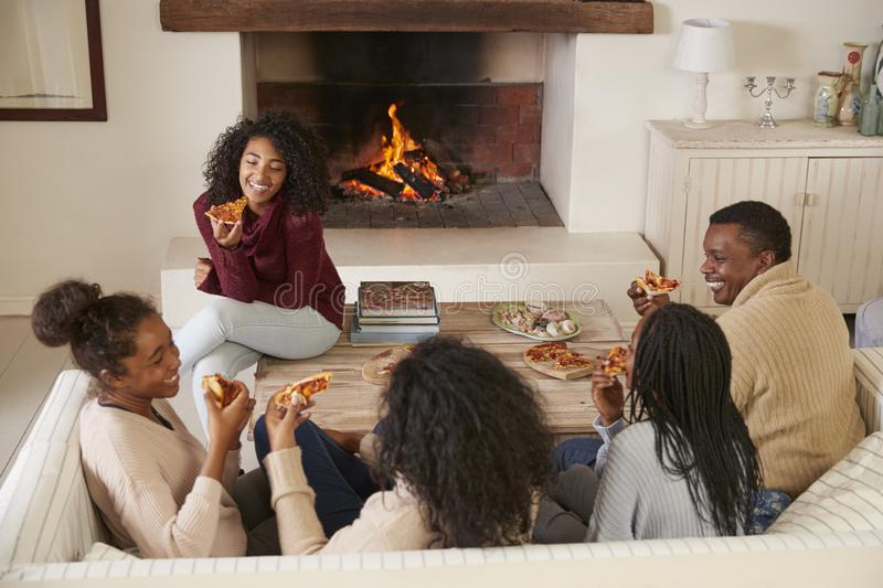 Family Sitting On Sofa In Lounge Next To Open Fire Eating Pizza stock photography