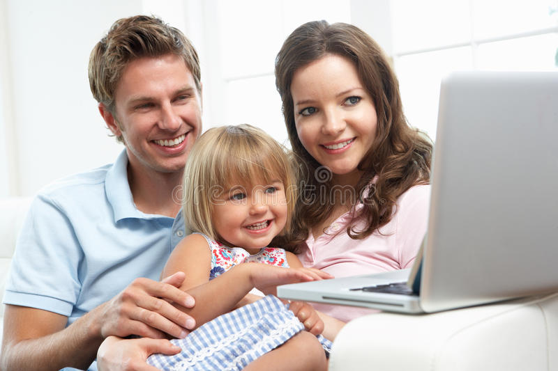 Download Family Sitting On Sofa Using Laptop At Home Stock Image - Image: 15586113