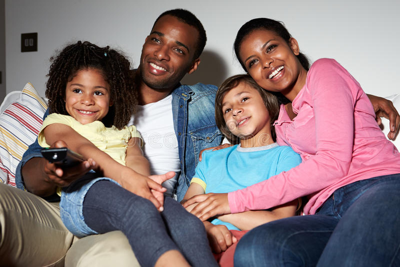 Download Family Sitting On Sofa Watching TV Together Stock Image - Image of laughing, evening: 35612257