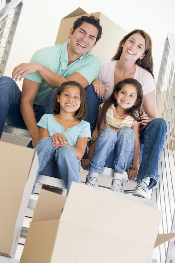Family sitting on staircase with boxes in new home. Smiling at camera stock photo