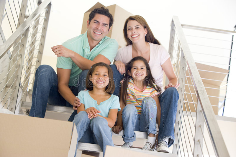 Family sitting on staircase with boxes in new home. Smiling royalty free stock image
