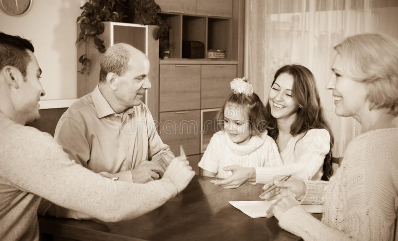 Family sitting at table with cards stock images
