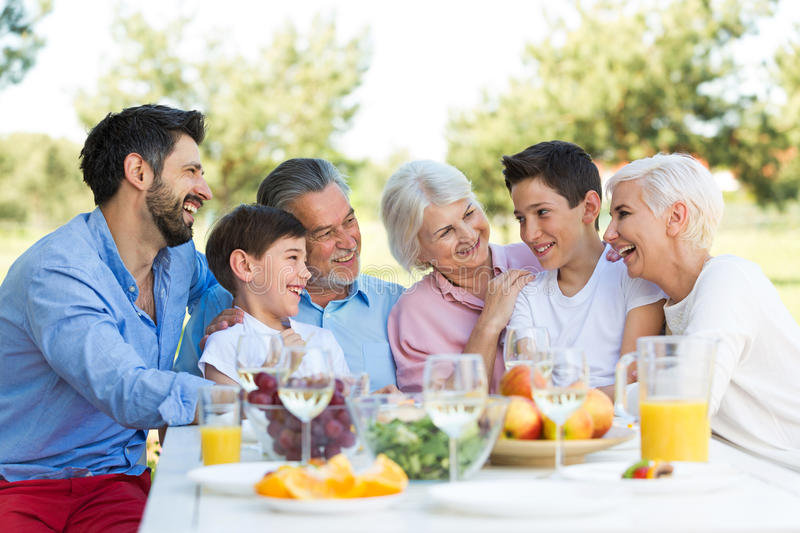 Family sitting at table outdoors, smiling royalty free stock photo