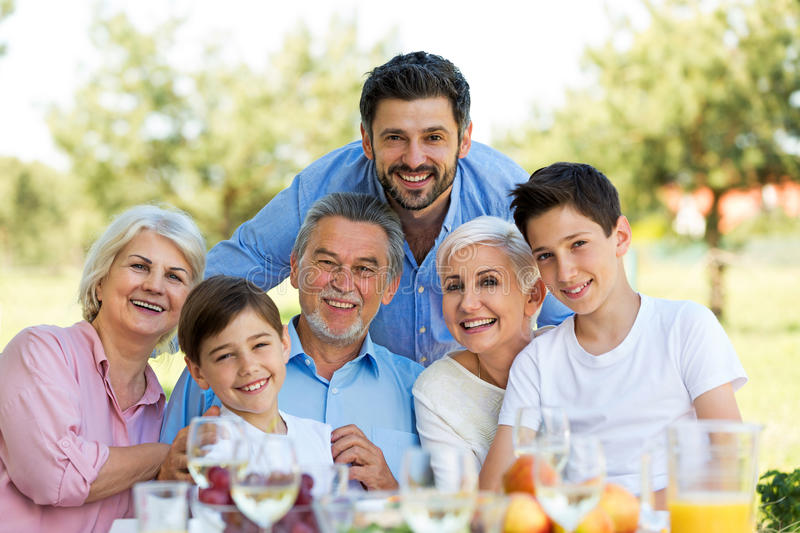 Family sitting at table outdoors, smiling stock photo