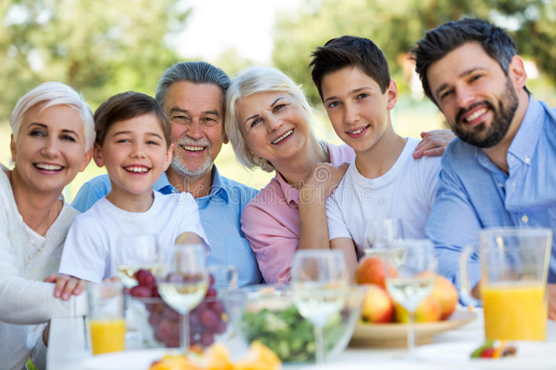 Family sitting at table outdoors, smiling. Family of three generations sitting at table outdoors, smiling royalty free stock image