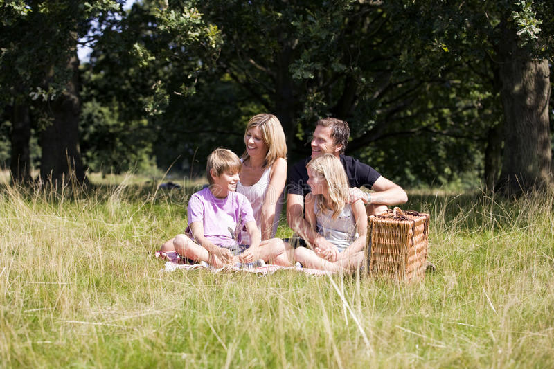 A family sitting together on the grass royalty free stock photo
