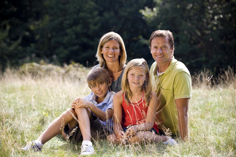 A family sitting together on the grass stock image