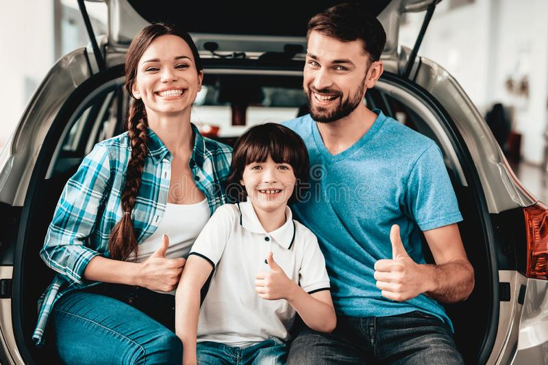 Family Are Sitting In The Trunk Of A New Car. Thumbs Up. Buying In A Showroom. Automobile Salon. Happy Together. Successful Choice. Good Mood. Great Trade royalty free stock photo