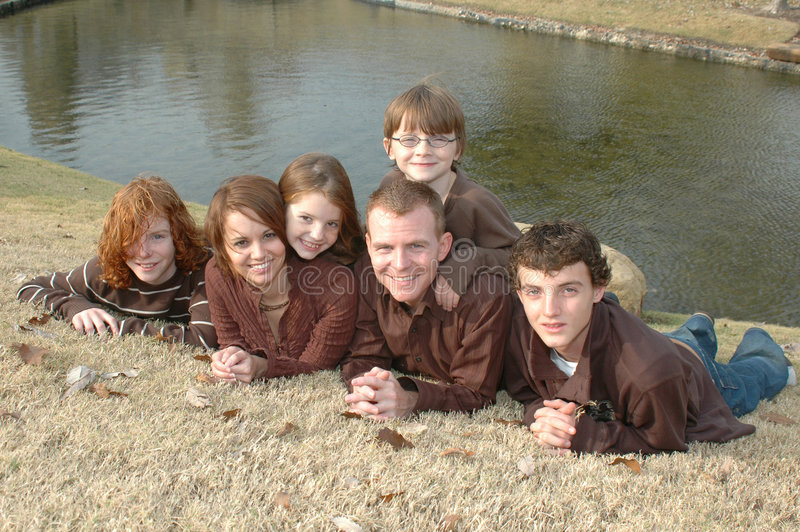 Family of Six. American family of three boys and one girl with mom and dad sitting in a park setting. Family making funny faces stock photography
