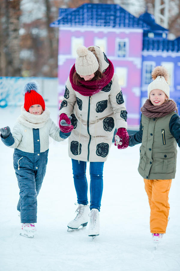 Family skating on ice-rink. Mother and kids learning to skate at winter. Smiling young mother and her cute little daughter ice skating together royalty free stock photos