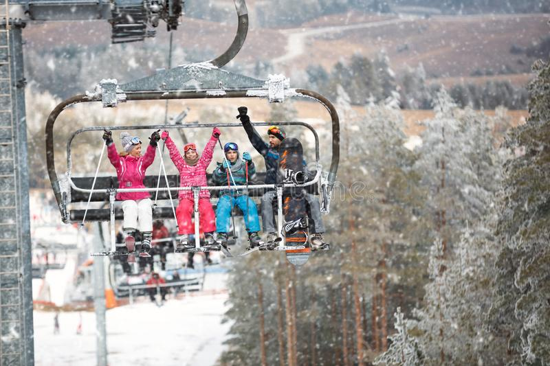family skier and snowboarder riding up to the top of the mountain on ski lift stock photo