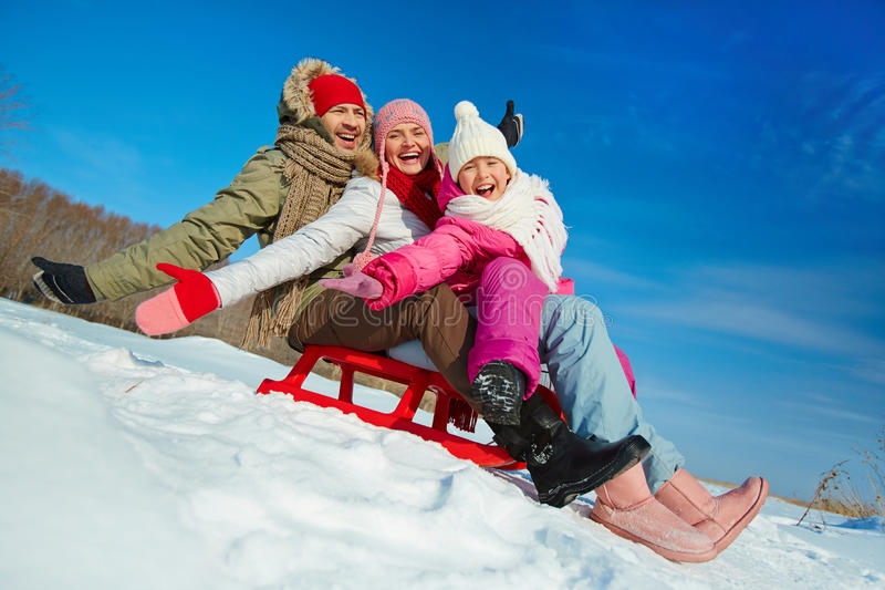 Family on sledge. Ecstatic family on sledge having fun in winter stock photo