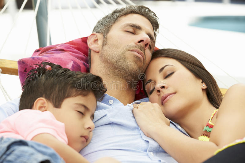 Family Sleeping In Garden Hammock Together stock images