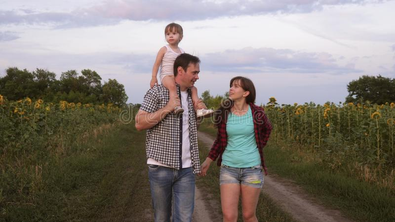 Family with small baby is walking along road and laughing next to field of sunflowers. Child is riding on his father stock photo