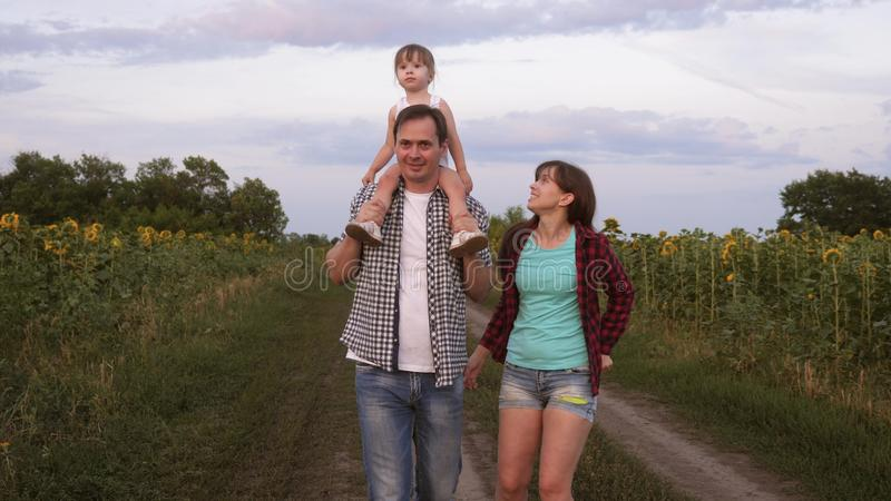 Family with small baby is walking along road and laughing next to field of sunflowers. Child is riding on his father stock photos