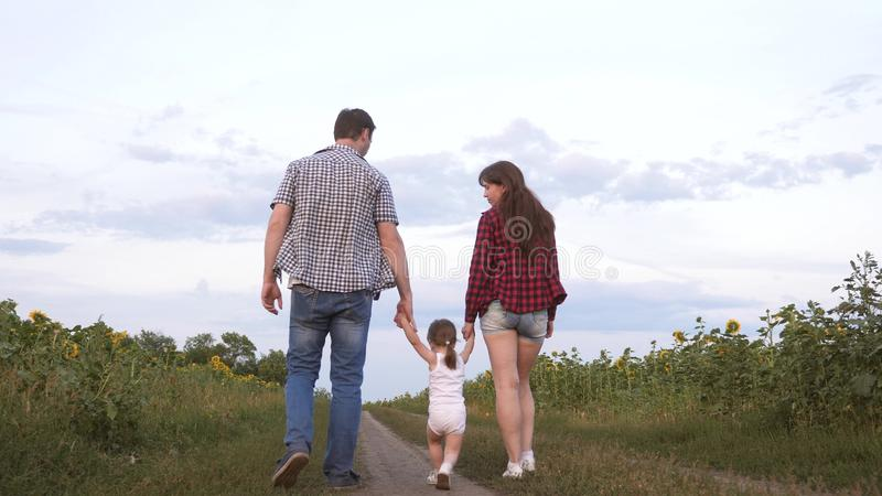 Family with small child walks along road and laughs next to field of sunflowers. Child is riding in arms of his father stock photos