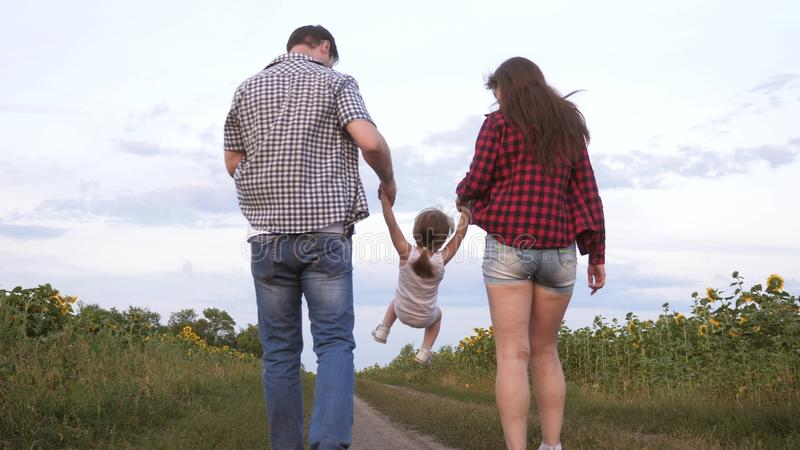 Family with small child walks along road and laughs next to field of sunflowers. Child is riding in arms of his father royalty free stock image