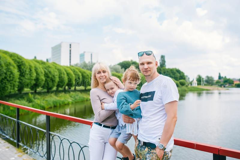 A family with a small children is photographed in a park on the shore of a river and on a bridge royalty free stock photo