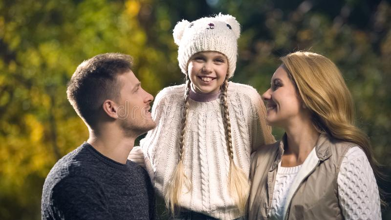 Family with smiling daughter posing for camera in fall park, health insurance stock photo
