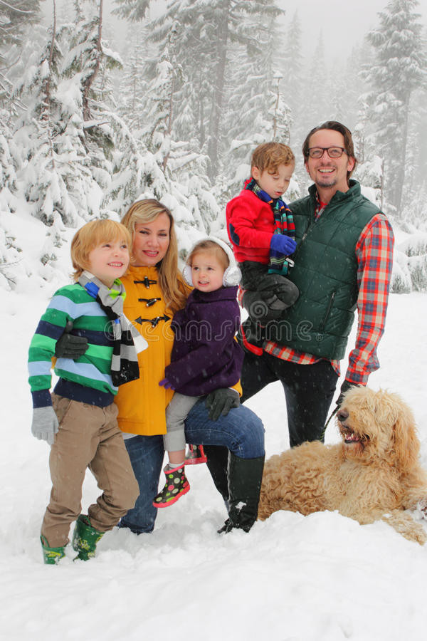 Family in Snow. A portrait of a family and their dog in the snow with snowy trees behind them, at Mt Hood Oregon. Shallow depth of field stock photography