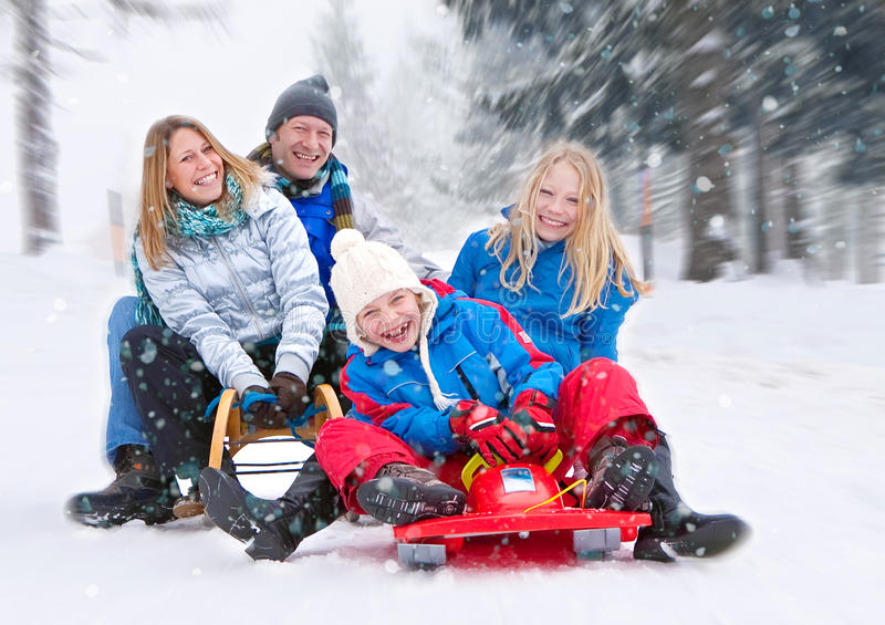 Family-snow-fun 01. Family is sledging in winterlandscape stock photography